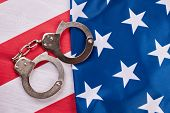 Handcuffs And American Flag. Pair Of Metal Handcuffs Lying On Usa National Flag. Law And Criminal. poster