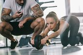 Male Personal Trainer Sitting With Timer And Young Sportswoman Doing Exercise With Abs Roller At Gym poster
