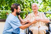 Geriatric nurse holding hand of happy old woman in rest home poster
