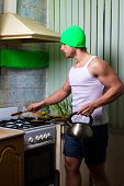 Fitness Man Cooking. Healthy Strong Muscular Sport Man Standing On Kitchen And Cooking. Strong Sport poster