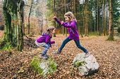 Identical Twins Are Jumping From Rocks In Forest On Hiking. poster