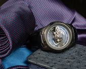 A Large Mens Watch Against A Pocket Square, Tie And Ostrich Leather Wallets poster