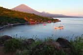 Volcano Agung (Bali, Indonesia) lighted by rising sun and calm lagoon with anchored sail boat