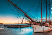 Helsinki, Finland. Old Wooden Sailing Vessel Ship Schooner Is Moored To City Pier, Jetty. Lighting A poster