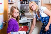 stock photo of homemaker  - Young housewife is doing the dishes with dishwasher - JPG