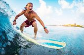 Young surfer rides the ocean wave in Maldives poster