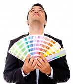 Pensive man holding a color guide - isolataed over a white backround