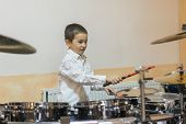 Boy Drumming. Boy In A White Shirt Plays The Drums. A Boy In A White Shirt Is Drumming poster