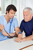 picture of bp  - Young male nurse checking blood pressure of a senior man at hospital - JPG