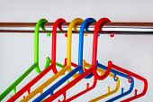 Close-up Of Multicolored Plastic Clothes Hangers On A Rod In The Closet. Set Of New Colorful Plastic poster