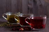 Healthy Lifestyle.hot Drinks.three Glass Cups With Black, Red And Green Tea With Dry Leaves And Flow poster