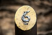Number Six On A Metal Post