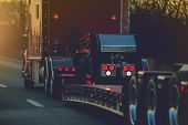 Semi Truck With Heavy Duty Platform Trailer On A Route. Transportation Industry. poster