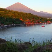 Volcano Agung (Bali, Indonesia) lighted by rising sun and calm lagoon with buildings on a coast