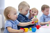Kids Group Playing With Play Clay At Nursery Or Kindergarten Or Primary School poster
