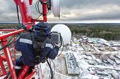Professional Industrial Climber In Uniform And Climber Equipment On The Telecommunication Tower Is I poster