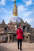 Young Girl Walks Towards A Sacred Buddhist Monastery. Sculptures Of Gods And Goddesses Carved On The poster