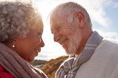 Head To Head Shot Of Loving Senior Couple Walking Outdoors Against Flaring Sun poster