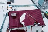 Worker Does The Installation Of The Roof Of The House. Installation Of Metal Tiles, Snow Retainers A poster