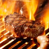 beef steak on the grill with flames.