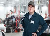 Auto mechanic with a wheel wrench in a workshop.