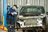 professional repairman worker in automotive industry at repair determination of damaged metal body c