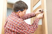 stock photo of carpenter  - Male handyman carpenter at interior wood door lock installation - JPG