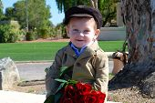 picture of one dozen roses  - sweet little boy waiting on a bench holding one dozen of red roses - JPG