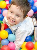 Niño feliz sentado en bolas de colores