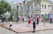 IRKUTSK,RUSSIA-Jun,16 2012:Kids run around in jets of the fountain in Jun,16 2012 in Irkutsk,Russia