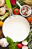 stock photo of peppercorns  - White frying pan with copy space for note or recipe surrounded by food ingredients - JPG
