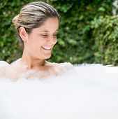 Beautiful woman relaxing in a bathtub and looking down