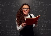 funny student with book can't understand her lessons. picture over chalkboard with formulas