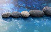 Row of zen rocks on blue splash background