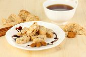 Aromatic cookies cantuccini and cup of coffee on wooden table close-up