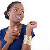 Beautiful african woman with perfume, young cheerful girl holding bottle of perfume and smelling aro