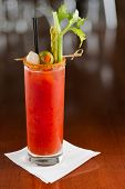 stock photo of bloody mary  - bloody mary cocktail isolated on a busy bar top garnished with onions olives asparagus and celery - JPG