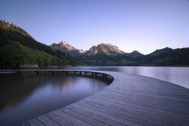 stock photo of semi-circle  - A semi circle shaped boardwalk on a mountain lake symbol for a turnaround situation - JPG
