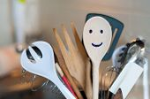 stock photo of ladle  - The wooden smiling spoon and kitchen accessories in the kitchen - JPG