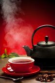 a cup of tea with teapot in the background