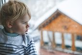 Little Toddler Boy Looking Out Of The Window On Winter Day With Snow Landscape.