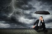 picture of bad mood  - a man in a suit and umbrella seeks shelter from flashes and rain - JPG