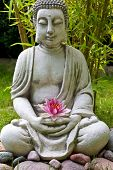 Buddha sculpture with lotus and bamboo