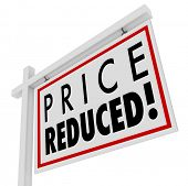 Price Reduced words on a home for sale sign to illustrate a home owner in distress and needing to sell immediately as a short sale or negotiated lower value to the right buyer