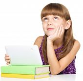 Wishful thinking young girl is using tablet while sitting at table, isolated over white