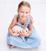 cute smiling girl in a blue dress with a white rabbit
