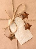 Closeup of a gift tag on a Christmas present. The package is wrapped in plain brown paper with a tie
