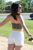 image of halter-top  - Pretty teen in white shorts and halter top walking through the park with out stretched arms