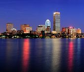 pic of prudential center  - Boston city skyline at dusk with Prudential Tower and urban skyscrapers over Charles River with lights and reflections - JPG