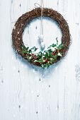 Rustic Christmas garland decorated with holly and berries hanging on white door